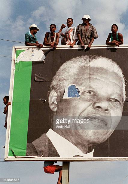 Children climb a massive billboard of ANC leader Nelson Mandela as they come out to greet him during South Africa's first democratic elections on...