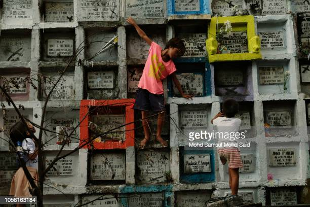 Children climb atop of tombs in a cemetery during the commemoration of All Saints' Day in Manila on November 1 2018 in Manila Philippines Filipinos...