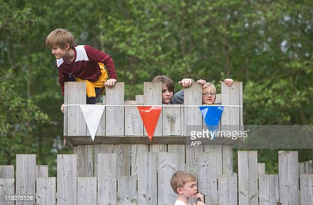 Children climb on a castle climbing frame at a Tea in the Park event in Kate Middleton's home village of Bucklebury on April 29 2011 AFP PHOTO/CHRIS...