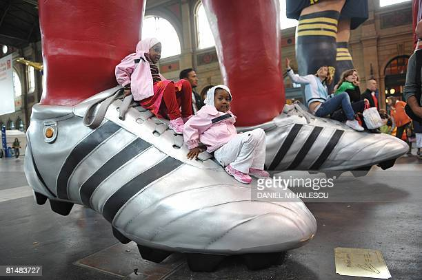 Children climb on the shoe of one of the giant statues of players from different national football teams, Michael Ballack and Philipp Lahm from...
