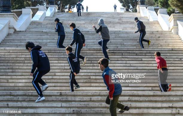 Children climb stairs by jumping on one leg while training in Baku on March 22 2019