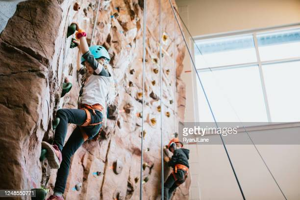 children climbing indoor rock wall - sport venue stock pictures, royalty-free photos & images