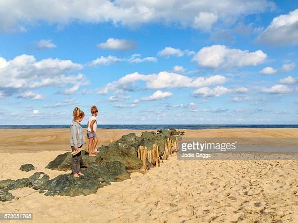 Children climbing on rocks at the beach