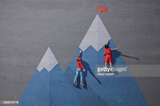 children climbing painted imaginary mountain - lebensziel stock-fotos und bilder