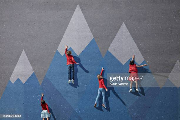 Children climbing painted imaginary mountains