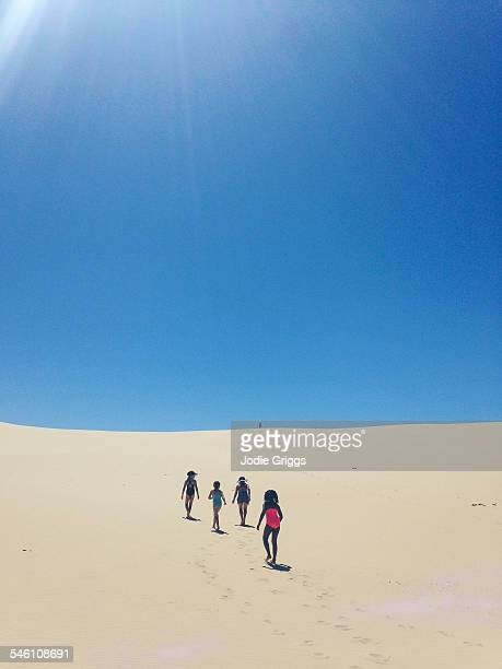 Children climbing to the top of a large sand dune