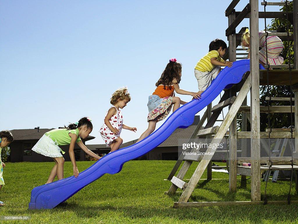 Children (4-6) climbing up slide in playground : Stock Photo