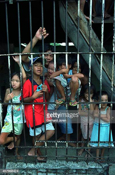 Children cling to the prison bars during visiting hours at Manila City Jail. Some children live with their fathers in their cells. The relatives of...