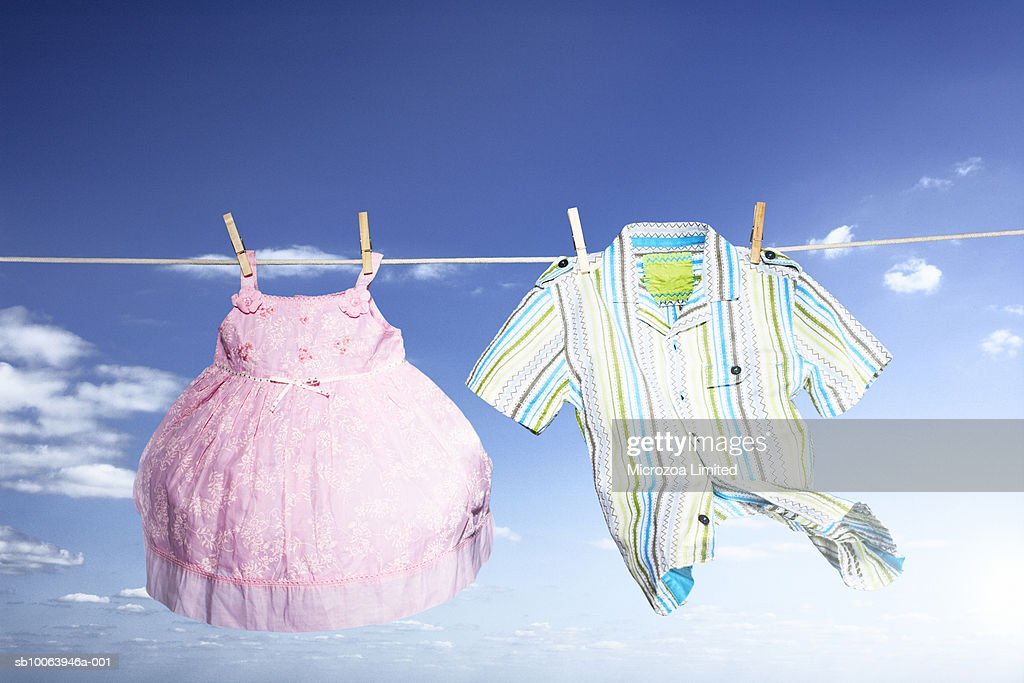 Children clothes hanging on washing line, low angle view : Stock Photo