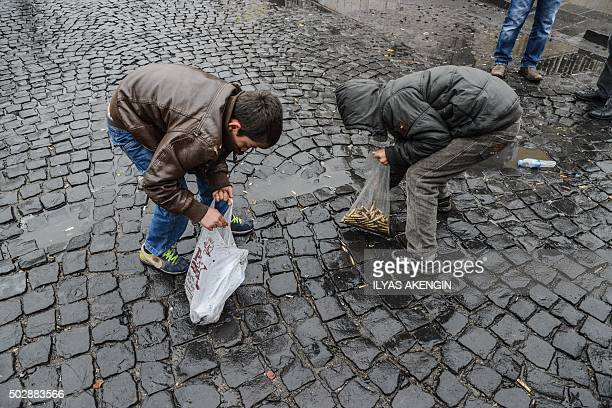TOPSHOT Children collect bullet shells off the streets of Sur district on December 30 2015 in the mainly Kurdish city of Diyarbakir after a curfew...