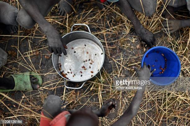 Children collect grain spilt on the field from gunny bags that ruptured upon ground impact following a food drop from a plane at a village in Ayod...