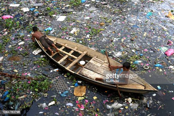 Children collect plastic bottle from polluted river Buriganga in Dhaka Bangladesh on July 03 2017 The River Buriganga which runs past Dhaka City is...