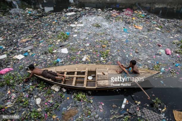 DHAKA BANGLADESH DHAKA BANGLADESH Children collect plastic bottle from polluted river Buriganga in Dhaka The River Buriganga which runs past Dhaka...