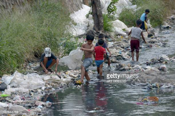 Children collect plastic to be sold and recycled at a polluted river in suburban Manila on February 8 2013 The city's trash disposal agency traps...