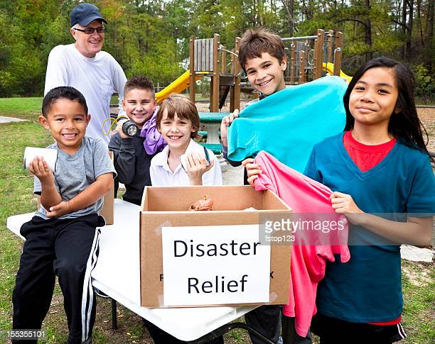 Children collecting donations for disaster relief victims. Park. Volunteers.