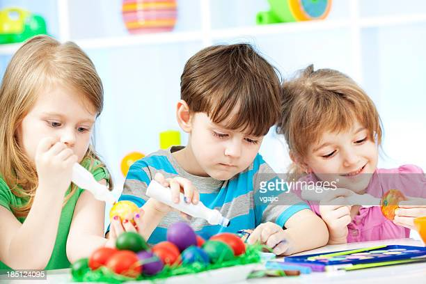 Children Coloring Easter Eggs