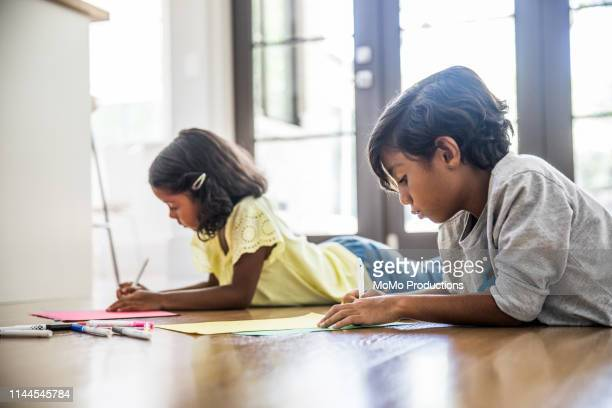 children coloring on floor - art and craft stock pictures, royalty-free photos & images