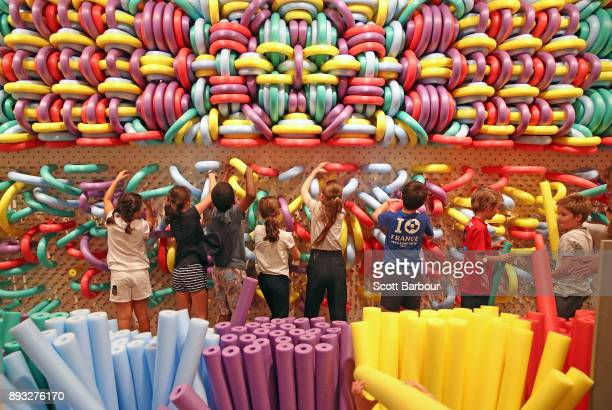 Children colourmatch a mural of pegs with pool noodles at an installation by the Dutch art collective 'We Make Carpets' during a media preview of NGV...