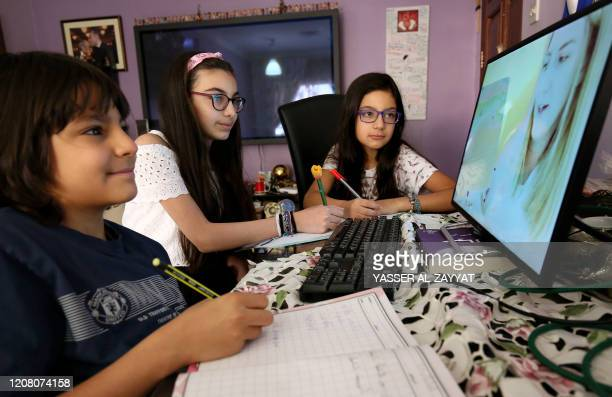 Children continue their school curriculum online via a computer screen at their home in Kuwait City on March 23, 2020. - Either on television as in...