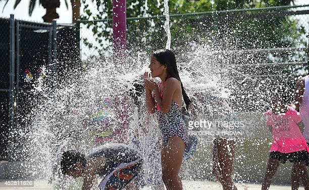 Children cool off at a water park in Alhambra California where water falls from a bucket above on July 27 as temperatures were hovering over 90...