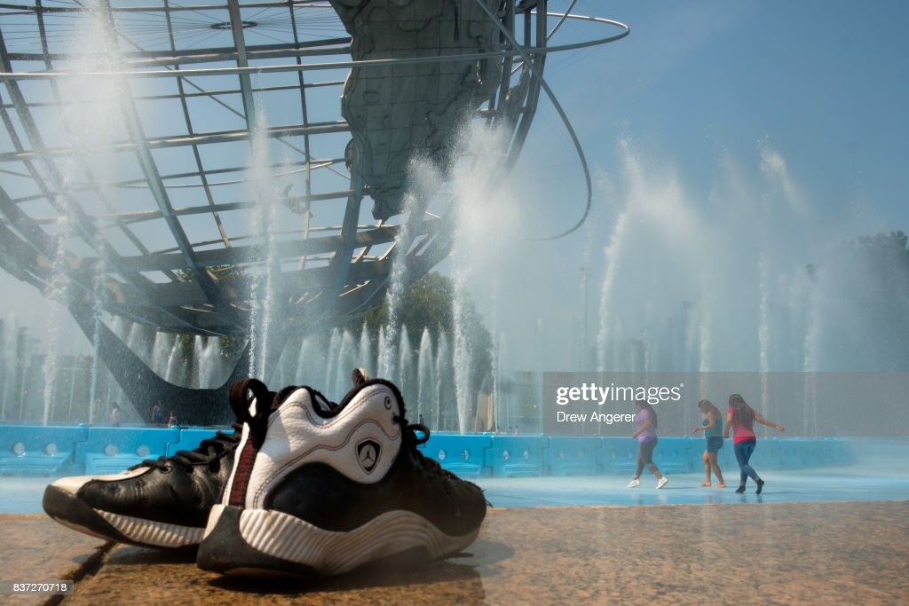 Children cool off in the fountains at the Unisphere steel structure at Flushing Meadows-Corona Park, August 22, 2017 in the Queens borough of New York City. With heat index values near 100, the New York City area is under a heat advisory on Tuesday.