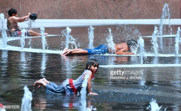 Children cool off in the water play area at Grand Park in Los Angeles California on July 5 2018 ahead of a coming heatwave in the Los Angeles area