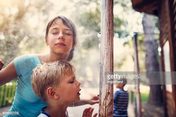Children cooling at water misting sprinklers in park