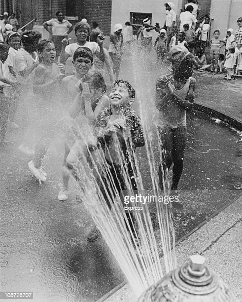 Children cooling off in the spray from a fire hydrant during a heat wave in Chicago circa 1965