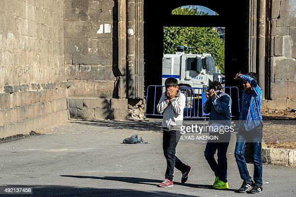 Children cover their eyes after Turkish riot police uses tear gas to disperse protesters gathered in Diyarbakir on October 10 after twin blasts at a...