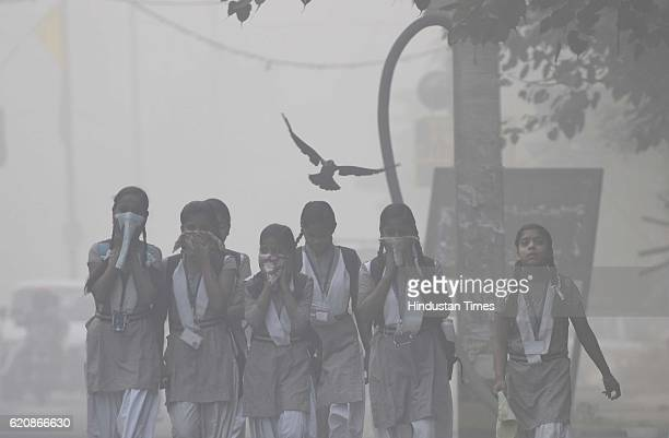 Children cover their face amid heavy smog in the early morning at Mayur Vihar area on November 2 2016 in New Delhi India A blanket of smog has...
