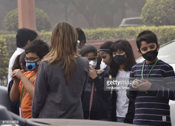 Children cover their faces with pollution mask due to dense smog which resulted in very less visibility on November 12 2017 in New Delhi India Air...
