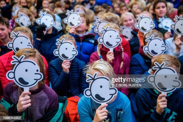 Children cover their faces with the fictional character Greg Heffley during a gathering with American cartoonist producer and author of children's...