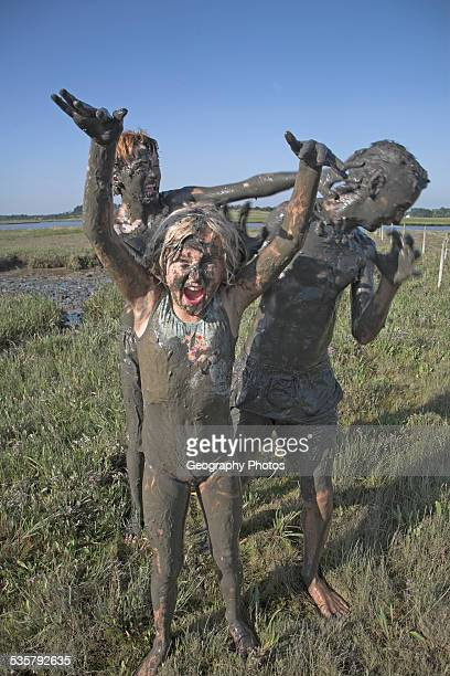 Children covered from head to toe in mud playing in pools of the Butley Creek river estuary Suffolk England no MR