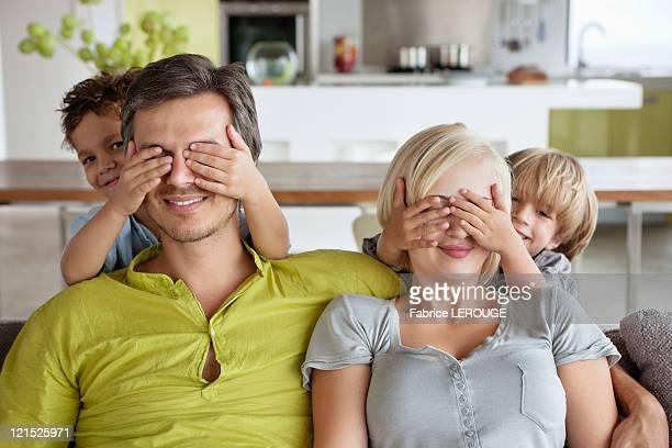 children covering parents eyes - mom flirting 個照片及圖片檔
