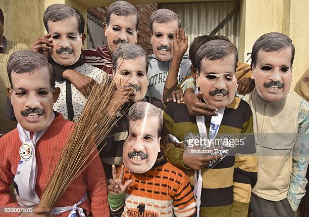 Children covering their face with Delhi CM Arvind Kejriwal's mask during an election rally at Naag Kalan village in Majitha constituency on January...