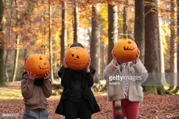 Children covering their faces with carved pumpkins.