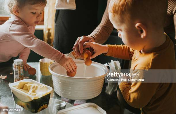 children cracking eggs into a mixing bowl - percussion mallet stock pictures, royalty-free photos & images