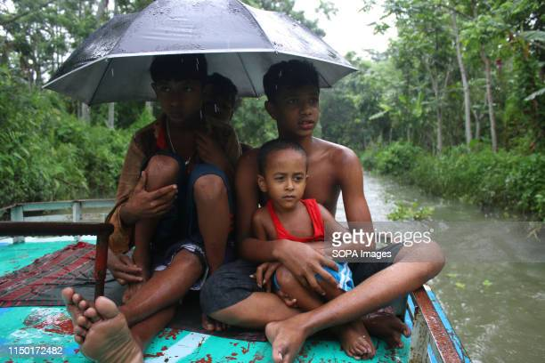 Children cross a canal on a troller boat during the first day of the monsoon season in Barisal Monsoon rain marks the arrival of Ashar the first...