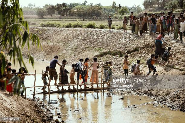 Children cross a makeshift bridge over a stream of sewage into nearby fields to play games There are now approximately 600000 Rohingya refugees in...