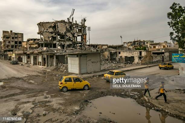 Children cross the road as cars drive by in the northern Syrian city of Raqa, the former Syrian capital of the Islamic State group, on May 1, 2019. -...