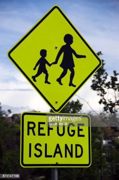 Children crossing and REFUGE ISLAND signs beside a road