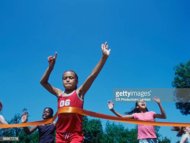 children crossing finish line in race - ziellinie stock-fotos und bilder