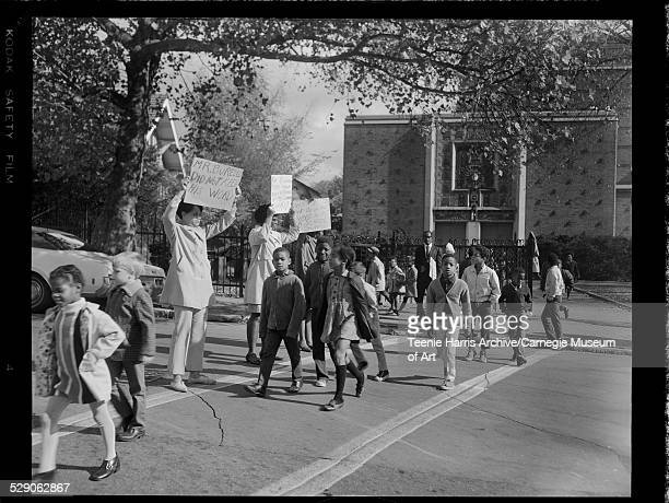 Children crossing street with adults holding placards protesting lack of crossing guard including one sign reading 'Mr Burrel did not keep his word'...
