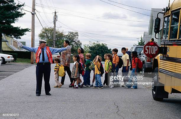 children crossing the street - traffic cop stock pictures, royalty-free photos & images