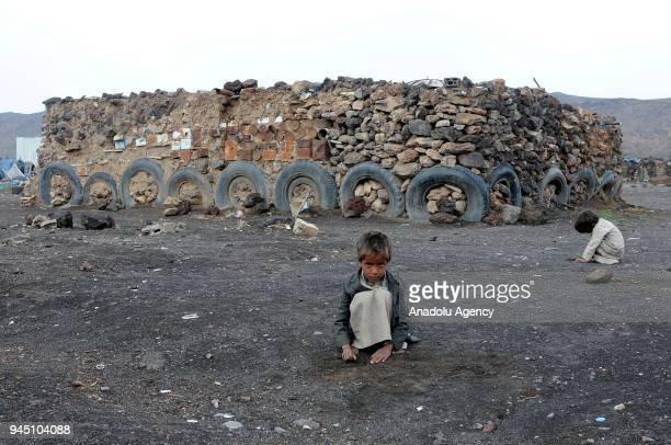 Children crouch at Darwan refugee camp in Amran north of Sanaa Yemen on April 11 2018 Yemeni families displaced by the clashes and airstrikes by...