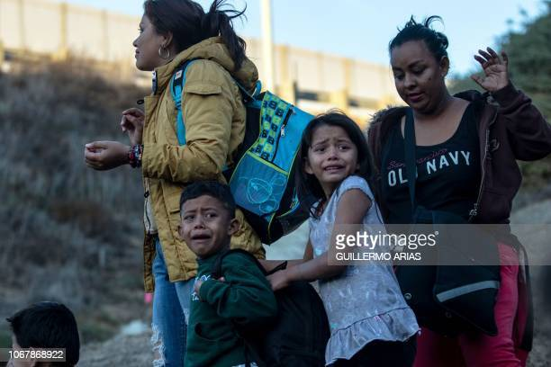 Children cry as a group of Central American migrants surrender to US Border Patrol agents after jumping over the metal barrier separating Playas de...
