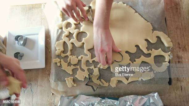 Children cutting cookies out of dough