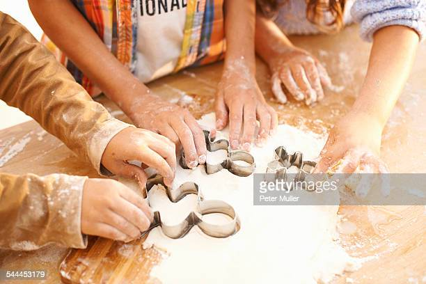 Children cutting shapes into dough in kitchen
