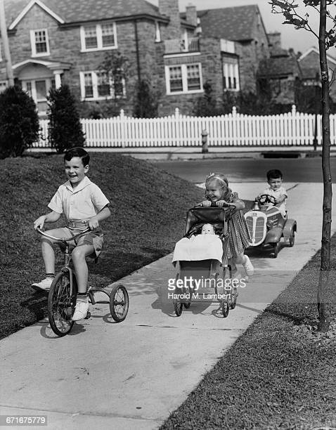 """ children cycling, driving and pushing pram in park"" - {{ collectponotification.cta }} foto e immagini stock"