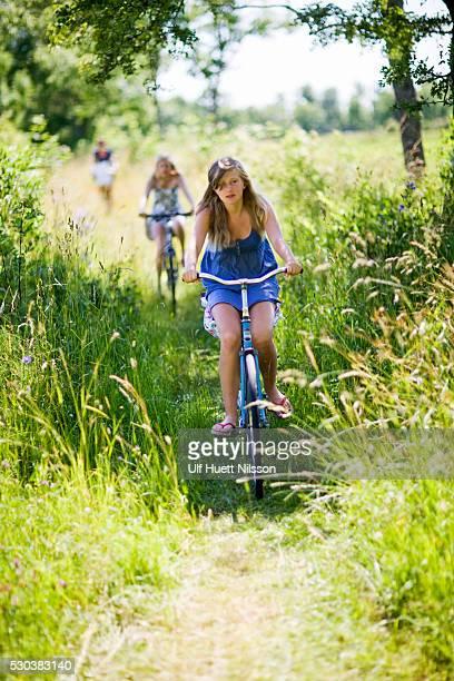 children cycling through field - エーランド ストックフォトと画像